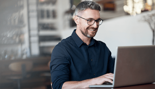 Man in blue shirt and glasses looking laptop screen